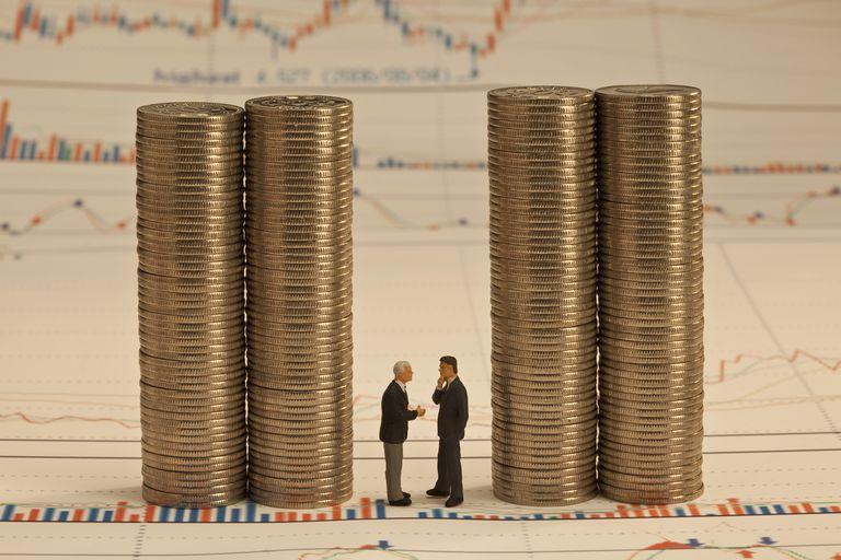 Two Men Talking Between Coin Stacks