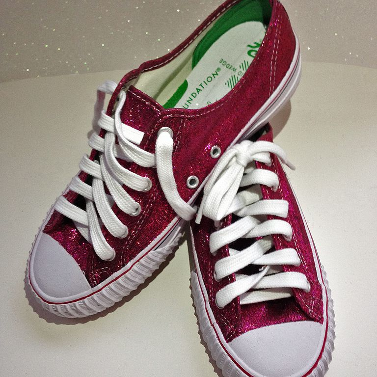Pair of red, glittered sneakers with white shoe laces and trim.