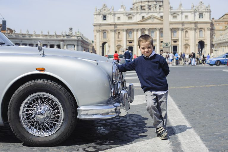 Young boy leaning against a luxury car