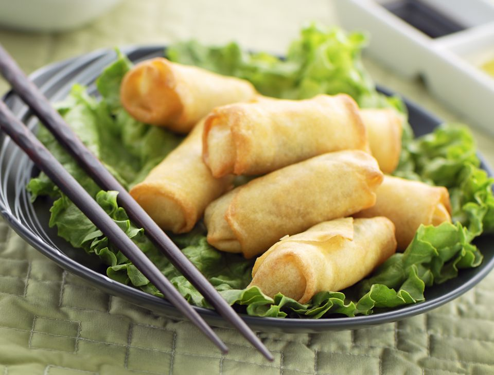 Dish of spring rolls on lettuce with chopsticks