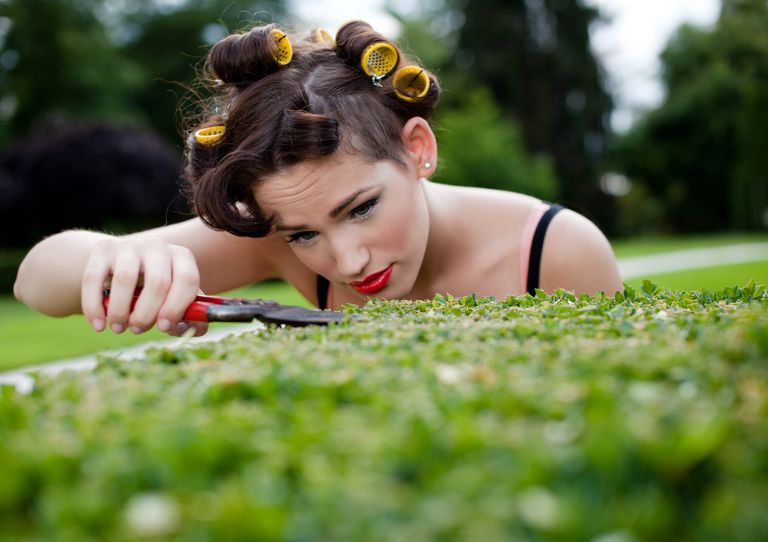Obsessive compulsive woman cutting grass with a scissors