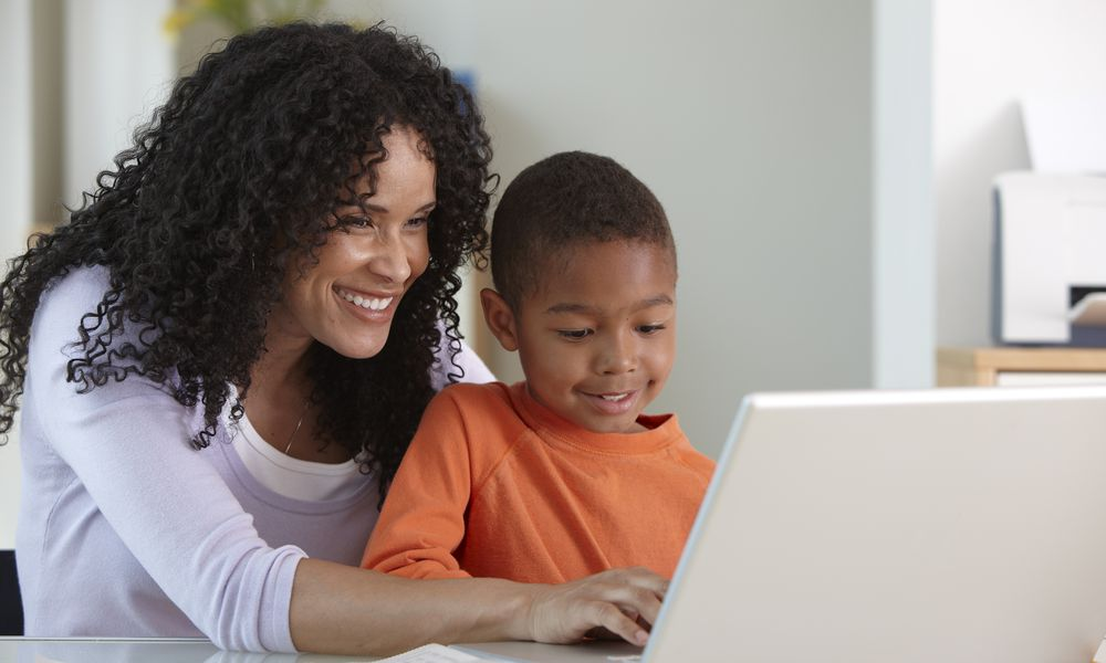 grades pressure - mom and son on computer, smiling