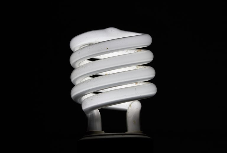 Close-Up Of Energy Efficient Lightbulb Against Black Background