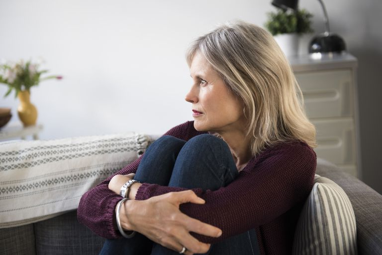 Worried woman sits on the couch.