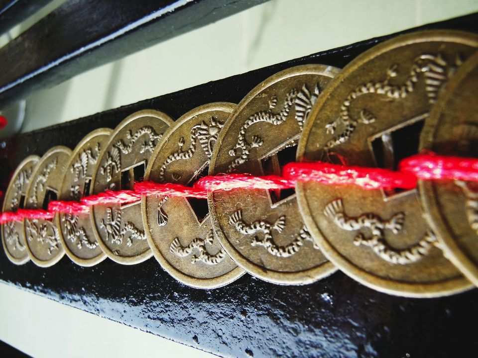 Close-Up Of Antique Feng Shui Coins Tied Up By Red Thread
