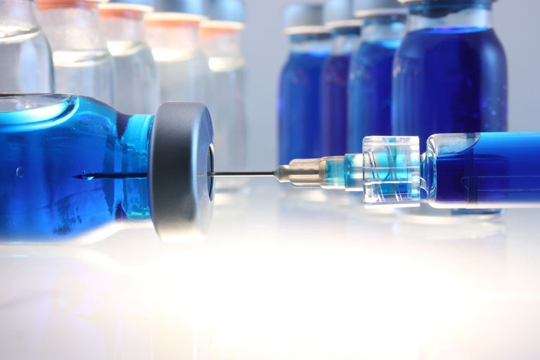 Syringe with blue liquid entering bottle with more behind