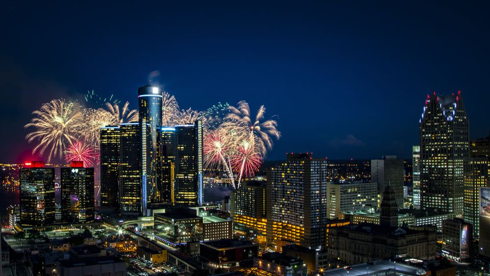 This image, shot from a rooftop, shows Detroit's Renaissance Center / GM Headquarters, silhouetted by a burst of fireworks over the Detroit River. In addition to the RenCen, the composition includes a significant portion of Detroit's skyline.