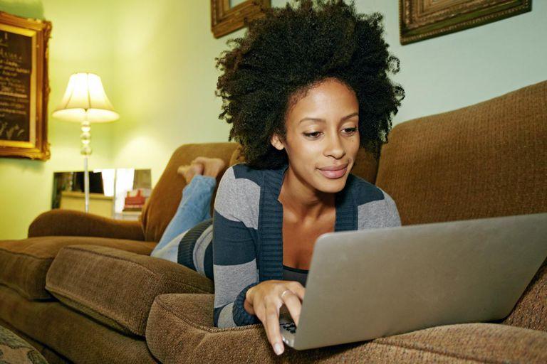 Mixed race woman using laptop on sofa