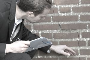 a man with a clipboard examining a crack in a wall