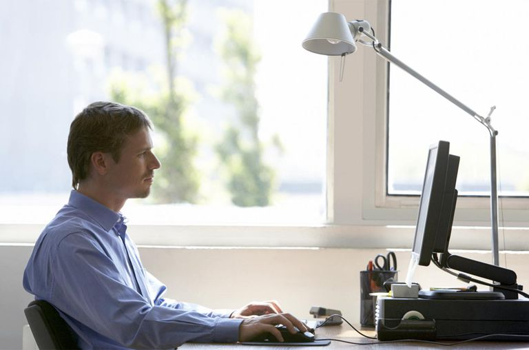 Man sitting at desk using computer, side view