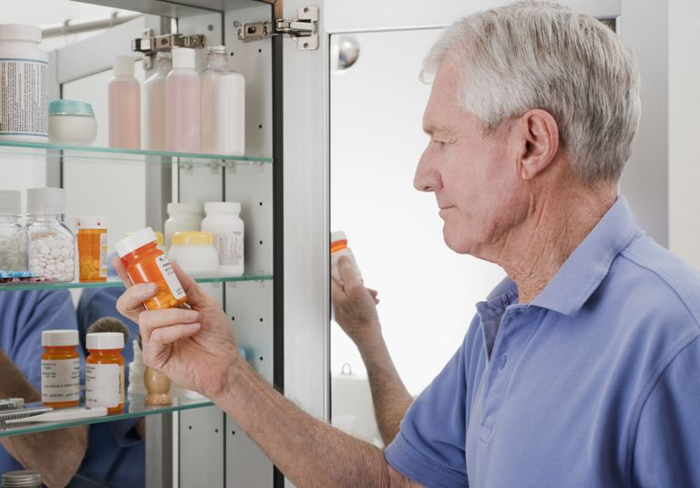 Man Looking Through Medicine Cabinet