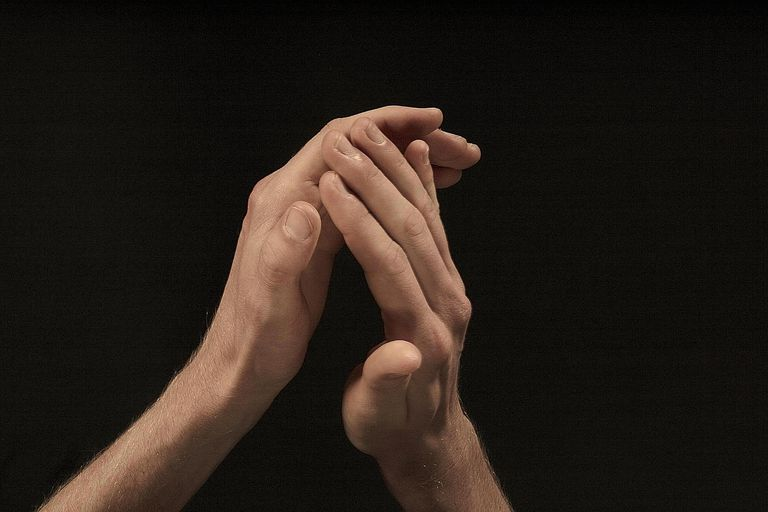 Close-up of man clapping hands against black background