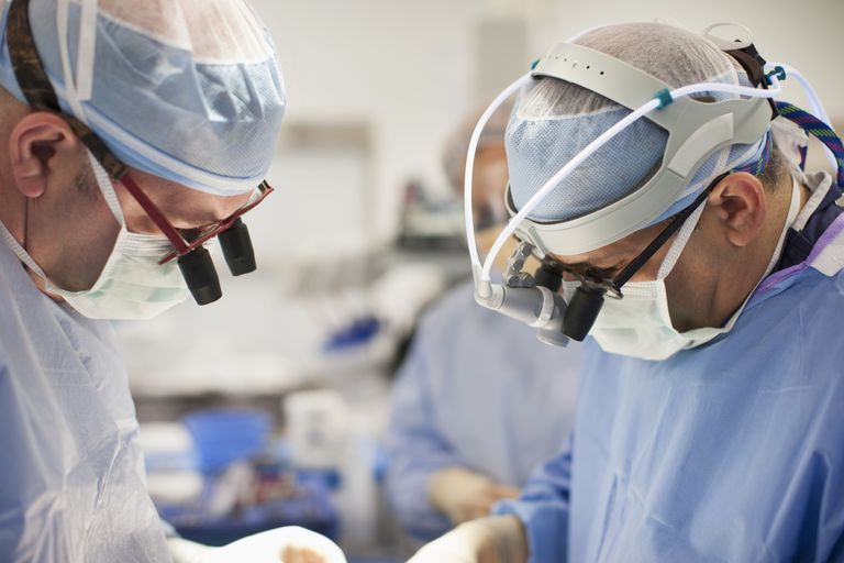 Surgeons wearing magnifying glasses in operating room