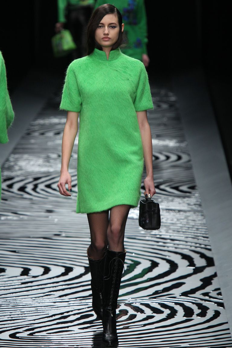 A model in a green shift dress walks the runway during the Shiatzy Chen Fall/Winter 2014 show.