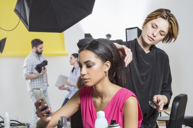 Hairdresser styling models long hair in photography studio