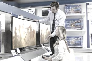 Salesperson Assists Woman Shopping For TV