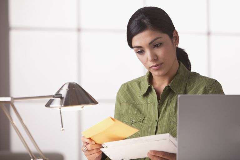 Hispanic woman looking at mail.