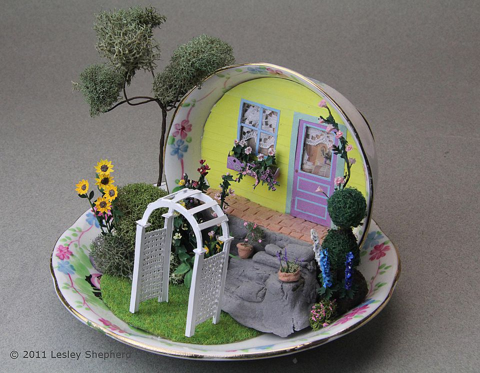 Quarter scale garden arbor set in a miniature garden scene in a tea cup.