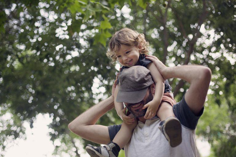 Dad carries boy in shoulders both looking happy
