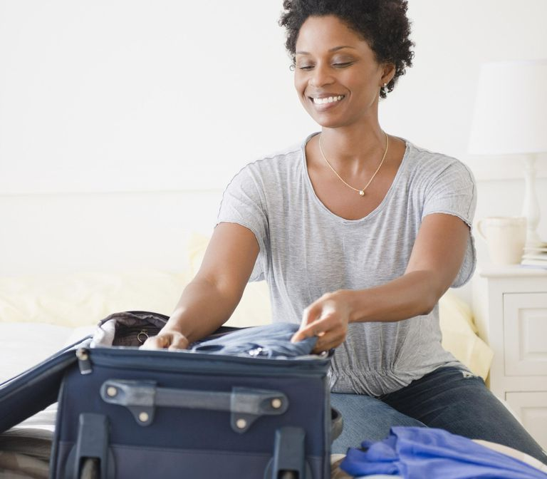 Black woman packing suitcase
