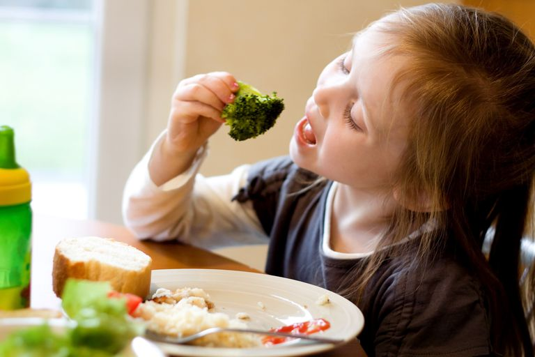 A young girl eating healthy vegetables