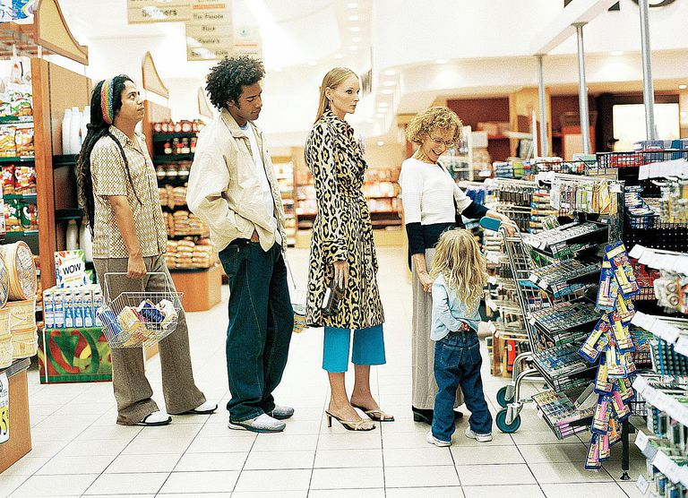 People wait in line to pay at a grocery store, demonstrating a common folkway in many societies.