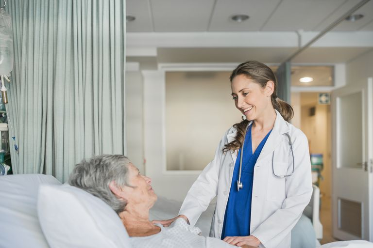 doctor talking to female patient in hospital bed
