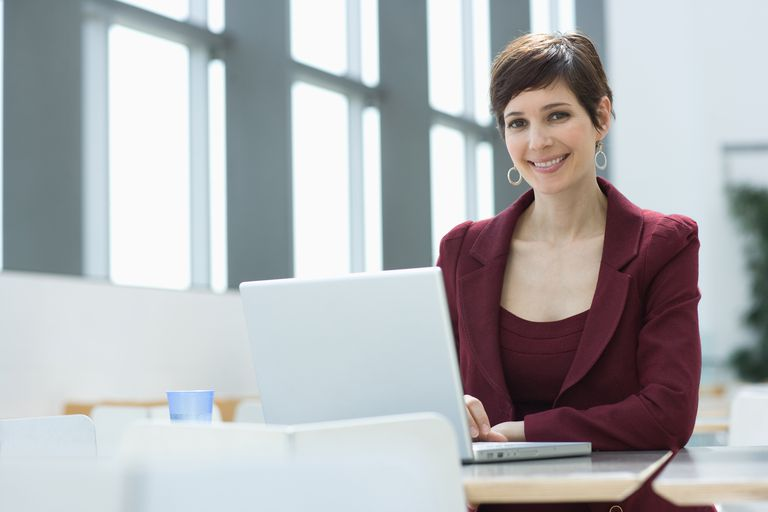 Smiling businesswoman using laptop to send out a welcome new employee announcement to share the employee's background and experience.
