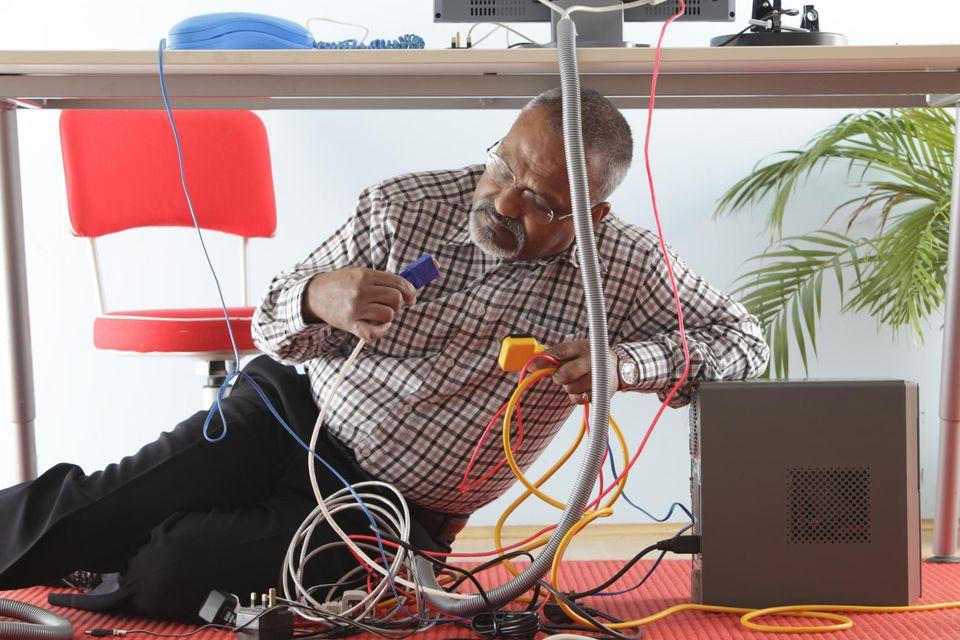 Man under desk with computer wires