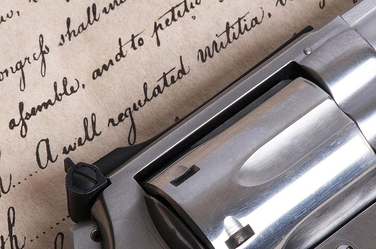 A handgun lays upon a copy of the United States Constitution, symbolizing the controversy over right-to-carry laws.