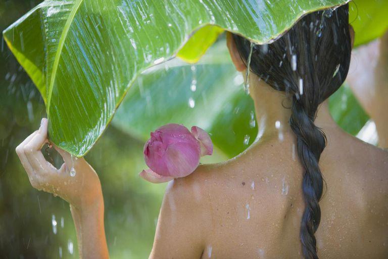 Teenage girl sheltering in tropical rain