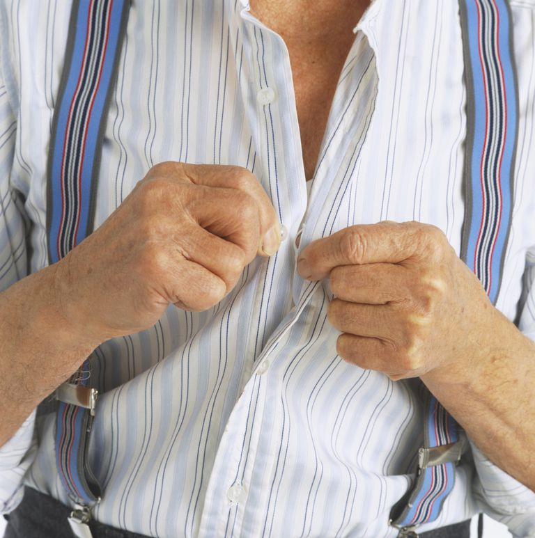 Elderly man in braces buttoning up his shirt.