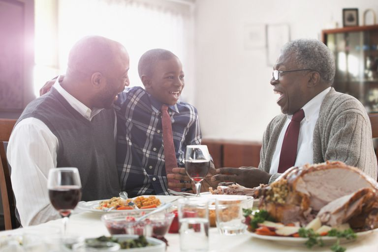 Three generations of men talking at holiday table