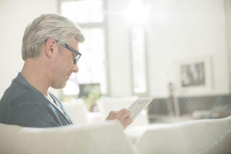 man looking at tablet on couch at home