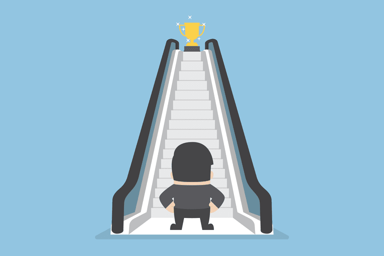 Man standing at bottom of escalator with trophy at the top