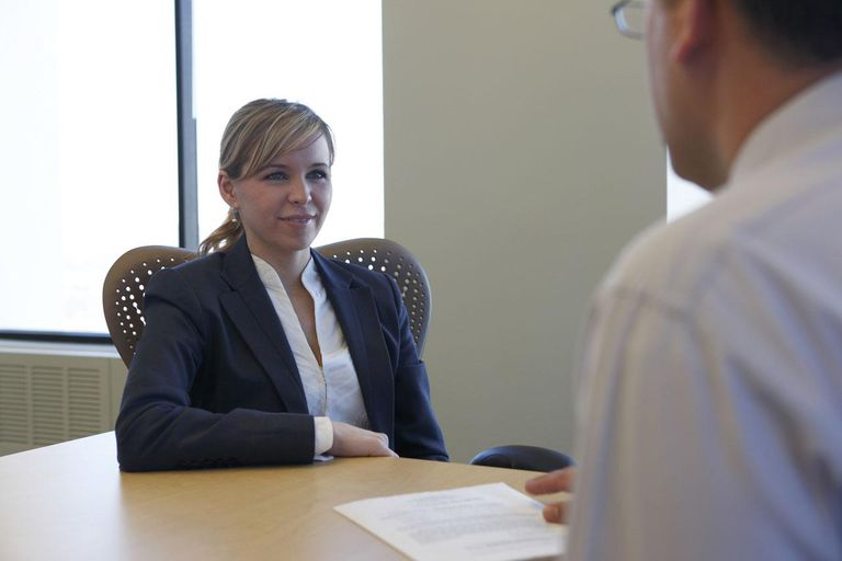 Man interviewing young woman in office