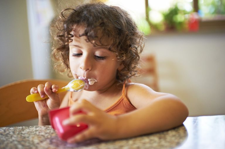 Toddler eating yogurt