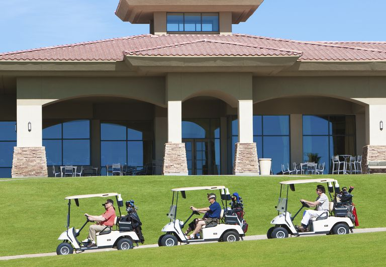 Golfers in carts pass in front of the clubhouse