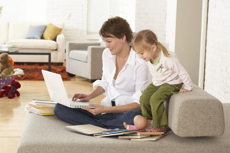 Woman using laptop on sofa by daughter (2-4) smiling.