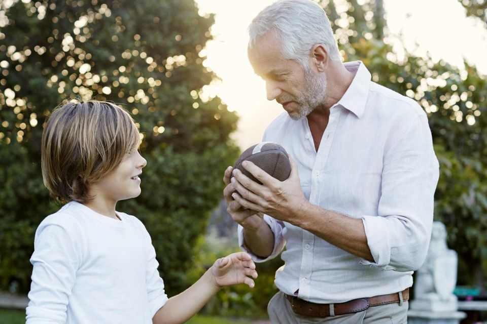 Grandfather Shows Grandson Football