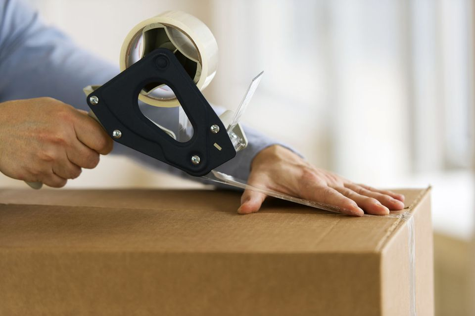 Man sealing a box closed with a tape dispenser