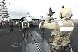 The Mediterranean Sea (Mar. 17, 2003) -- An Aviation Boatswain's Mate guides an F/A-18C Hornet from the 'Valions' of Strike Fighter Squadron Fifteen (VFA-15) into position for launch.