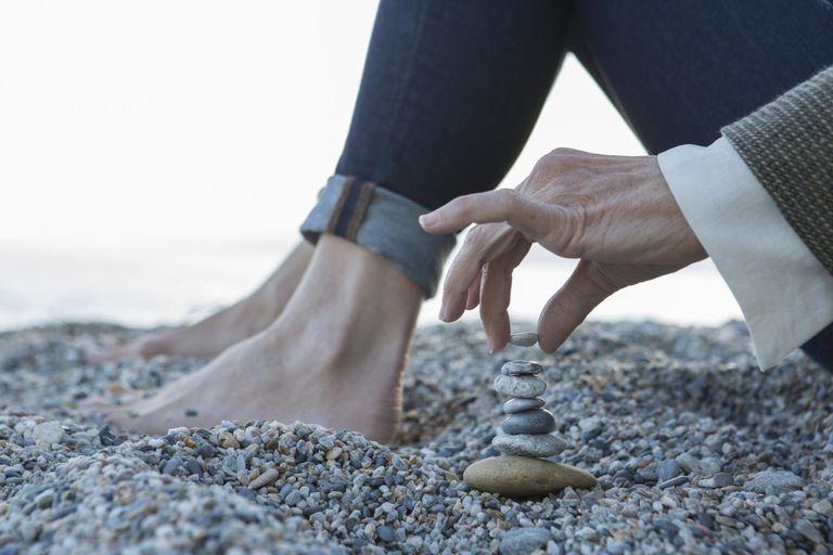 Cloe-up view of woman stacking pebbles, at beach