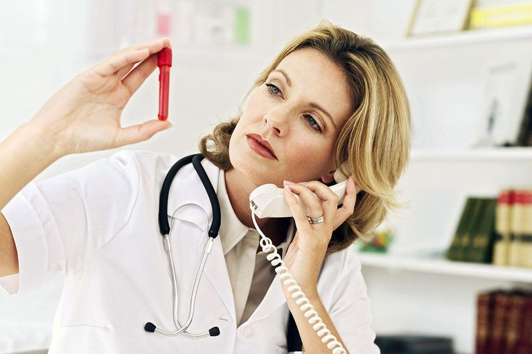 Young female medical professional holding a test tube and talking on a telephone