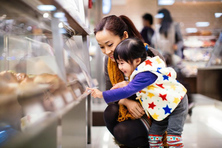 Mom & toddler girl shopping bread in the b...