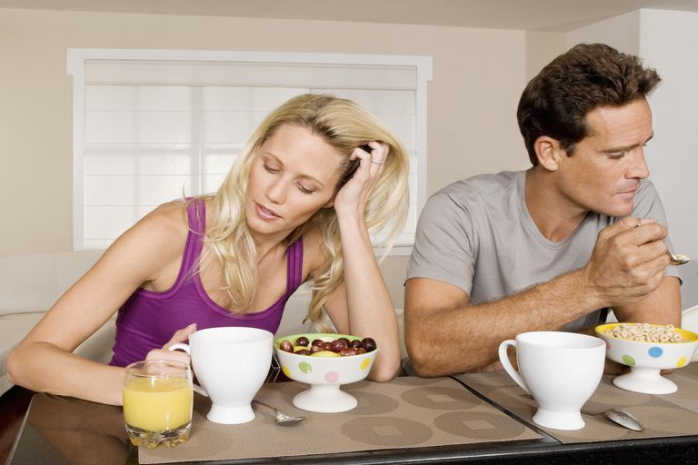 Couple ignoring each other at breakfast