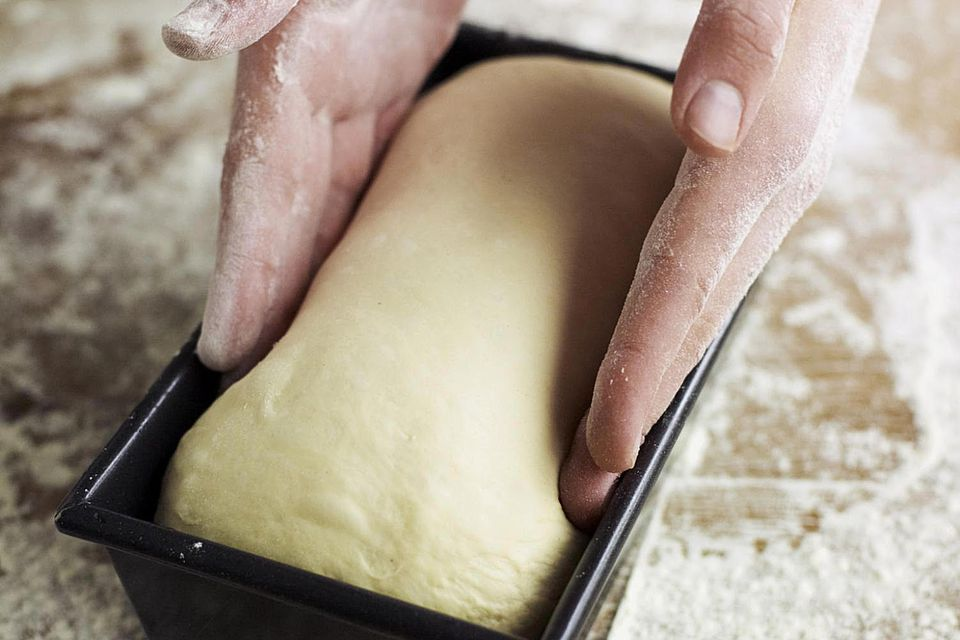 Placing partially risen bread dough in loaf tin