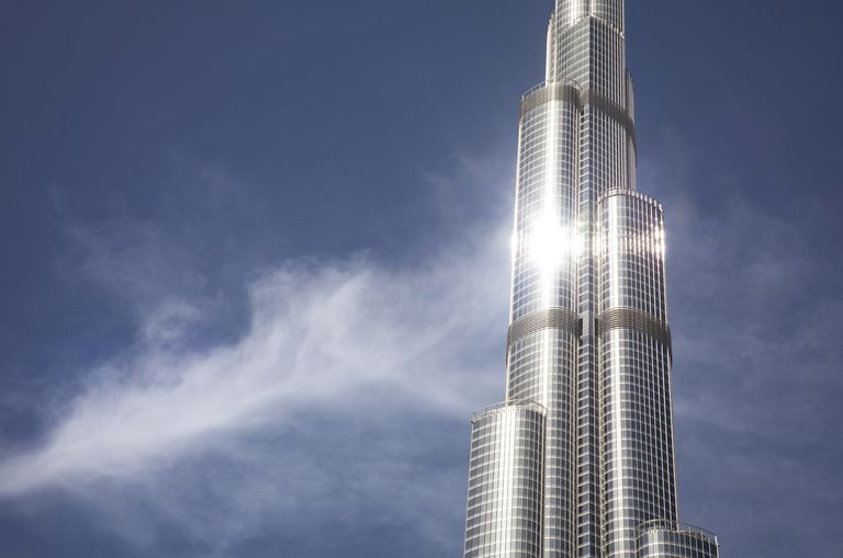 Detail of the stainless steel facade of the world's tallest building, in the clouds with sun reflecting Dubai