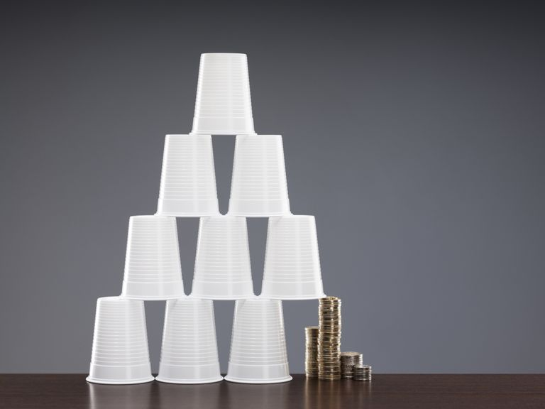 Coins holding up one side of a cup pyramid