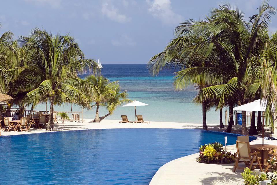 Resort pool overlooks a tropical beach on the island of Roatan, Honduras